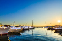 Luxury Yachts, Sailing And Motor Boats Docked In Sea Port At Sunset.