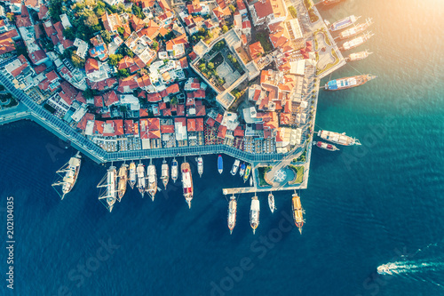 Aerial view of boats, yachts, floating ship and beautiful architecture at sunset in Turkey. Landscape with boats in marina bay, sea, buildings in city. Top view of harbor with sailboat and houses.