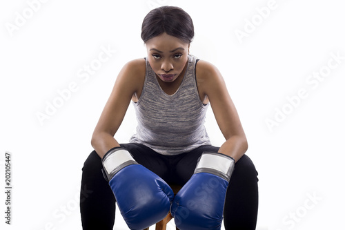 Black female as a gritty woman with boxing gloves for box aerobics or martial arts and self-defense. She is putting on a game face white sitting down to show determination. On a white background.