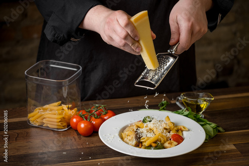 Male chef  hands close-up rubbed Parmesan cheese on a ready penne pasta in a white plate, on a wooden table with cherry tomatoes, basil and olive oil.