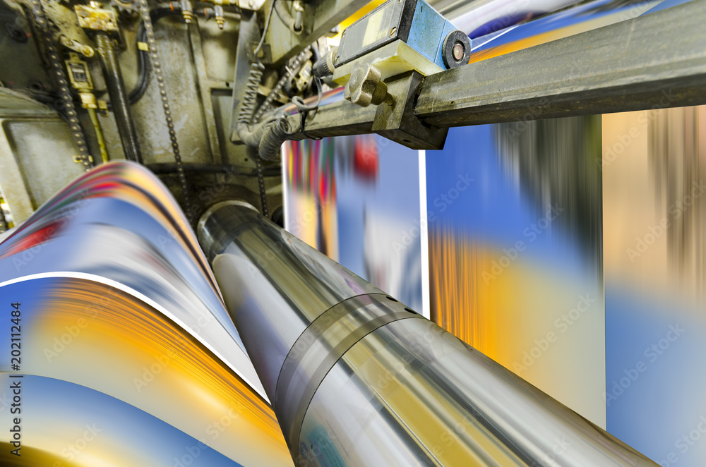 Fototapeta A large offset printing press running a long roll off paper over its rollers at high speed