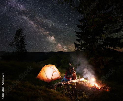 Foto op Aluminium Kamperen Man pointing to the incredible beautiful starry sky and Milky way. Couple sitting near the glowing tent, trees and bonfire at log in mountains. Romantic evening camping under the fabulous starry sky