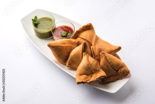 Veg Samosa is a triangle shape pakora stuffed with Aloo sabji, served with green chutney and tomato sauce. selective focus