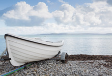 Small White Dinghy On A Trailer Close To The Sea