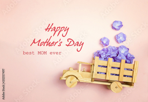 Mothers day greeting message with wooden toy truck with violet mothers day greeting message with wooden toy truck with violet flowers in the back on pink m4hsunfo