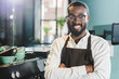 cheerful african american barista in apron and eyeglasses standing with crossed arms and smiling at camera in cafe