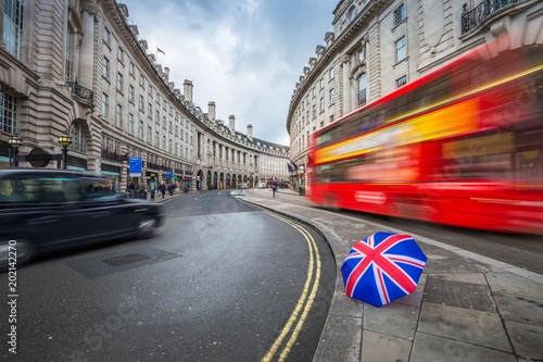 Fotografía London, England - Iconic red double-decker bus and black taxi on the move on Reg