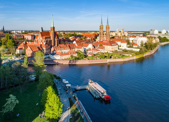Fototapeta Poland. Wroclaw. Ostrow Tumski, Gothic cathedral of St. John the Baptist, Collegiate Church of the Holy Cross, Archbishop's palace, tourist harbor, ship and Odra (Oder) River. Aerial view at sunset