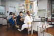 Young university students sitting on chairs in chemistry laboratory