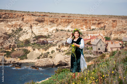 on a high seashore cheerfully walks a round charming woman in a wreath of flower Canvas Print