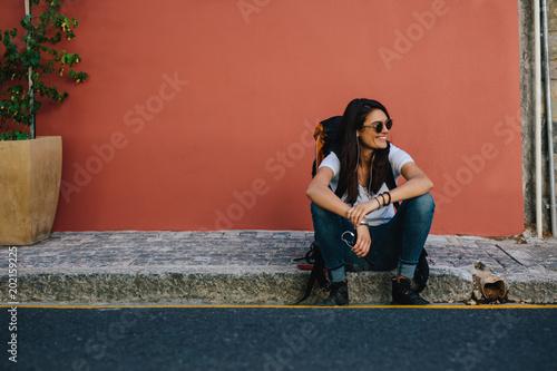 Female traveler resting on the sidewalk