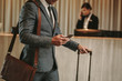 Leinwanddruck Bild - Businessman in hotel lobby with phone and luggage