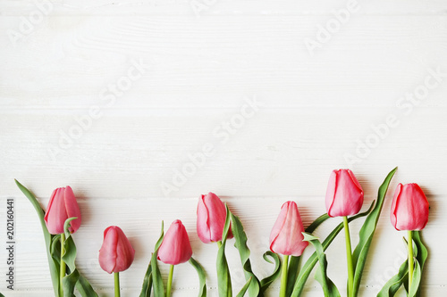 Foto op Plexiglas Tulp Bunch of pink tulip in beautiful spring holidays composition lying on white wooden textured table background. Mother's day bouquet arrangement. Flowers for women's day. Copy space, close up, top view.