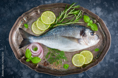 In de dag Vis Fresh raw Dorado fish with fresh herbs, spices, lime, top view, horizontal