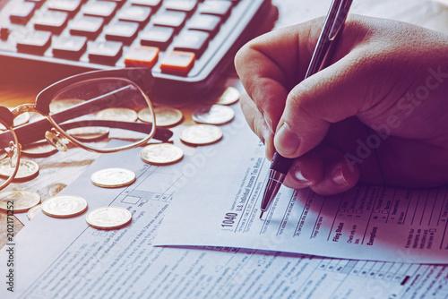 Fototapeta Tax day.Man filing US tax form. tax form us business income office hand fill concept. obraz