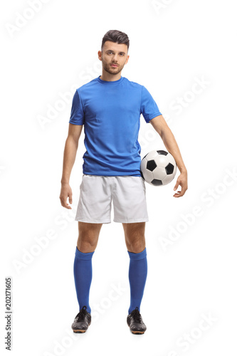 Soccer player holding a football and looking at the camera
