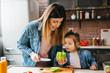 Leinwanddruck Bild Mother cook with daughter on kitchen,cut green pepper.