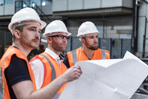 Three men wearing hard hats and safety vests holding plan in factory