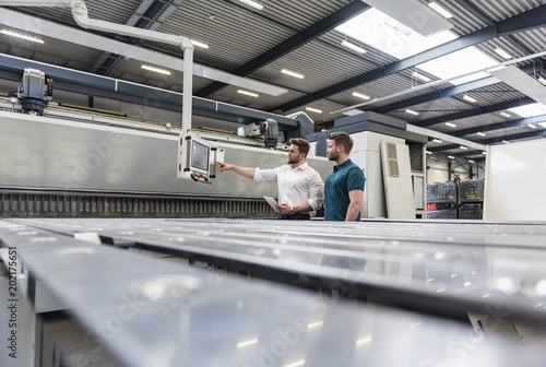 Two men looking at screen on factory shop floor