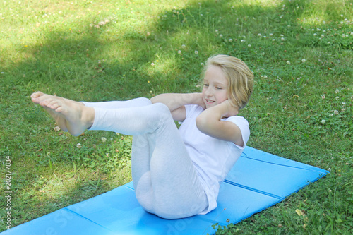 Beautiful blonde preteen girl in light clothing practicing yoga on a mat in the park. Healthy lifestyle. Outdoors workout.