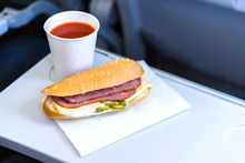 Economy Class Inflight Meal, Sandwich And Tomato Juice On The Folding Table