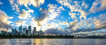 Wide Panorama Of Sydney, Australia With Amazing Sunset And Clouds Over The City Skyline And Botanic Gardens