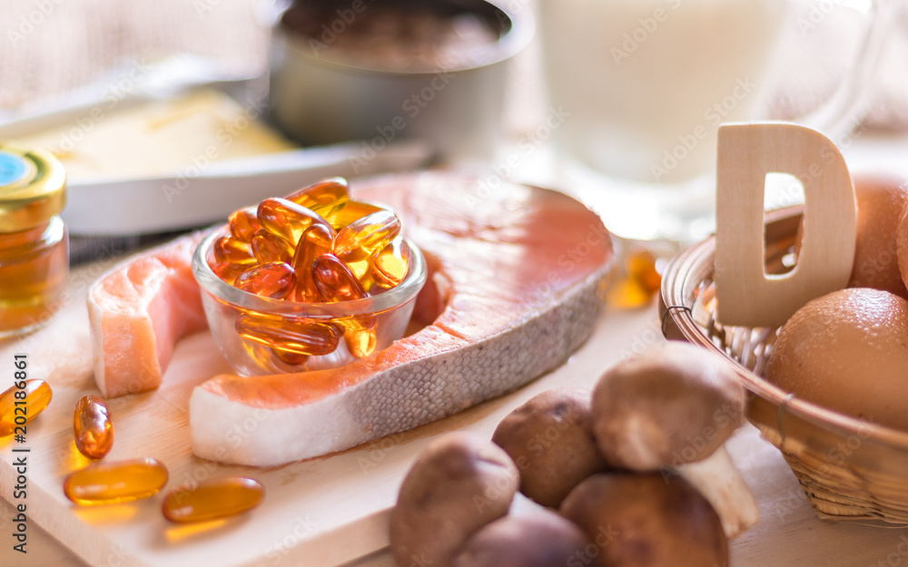 Fototapeta Natural source of vitamin D in Salmon, eggs, mushroom, fortified milk, margarine, canned tuna and fish oil capsule on wooden texture and background, healthcare and supplemental concept