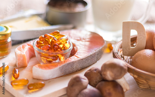Fototapeta Natural source of vitamin D in Salmon, eggs, mushroom, fortified milk, margarine, canned tuna and fish oil capsule on wooden texture and background, healthcare and supplemental concept obraz