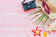 Beach accessories including sunglasses, sunscreen, hat beach, shell, green coconut palm leaves tree and retro camera on bright pink pastel wooden background for summer holiday and vacation concept.