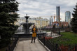 A young woman stands near a fountain in the background of the city of Yekaterinburg