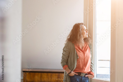 Fotografie, Obraz  Attractive middle-aged woman standing with her hands in her pockets of her jeans