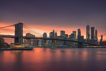 Sławny Brooklyn most w Nowy Jork z pieniężnym okręgiem - w centrum Manhattan w tle. Zwiedzająca łódź na East River i piękny zachód słońca nad karuzelą Jane's.