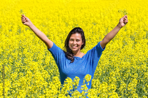 Fotobehang Zwavel geel Happy woman arms up in rapeseed field