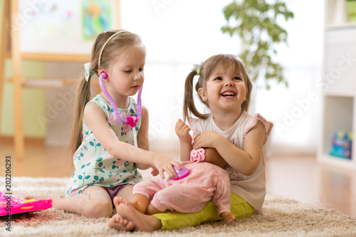Fototapeta Two children kids friends playing doctor with a doll in kindergarten