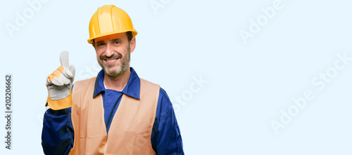 Senior engineer man, construction worker pointing away side with finger isolated over blue background