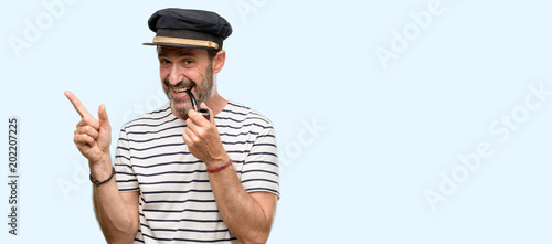 Sailor captain man smoking a tobacco pipe pointing away side with finger isolate Fototapete