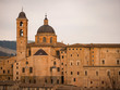 view at sunset of the beautiful and ancient city of Urbino, UNESCO World Heritage, with a dome and bell tower illuminated by the warm light of the spring sun.