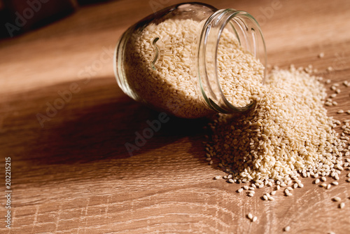 Photo Glass jar with sesame lying on wooden kitchen table