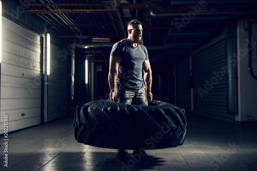 Portrait side view of strong muscular bearded short hair bodybuilder