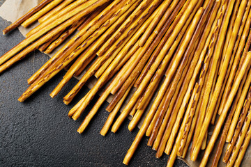 Salted bread sticks or long crunchy salty pretzel sticks on parchment paper o...