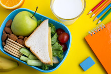 School Lunch In The Box, Milk In The Glass And Notebook On The Yellow Background.Top View.