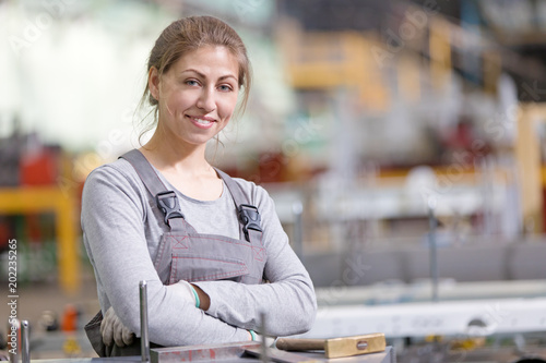 Smiling production female worker at workplace on manufacture workshop background