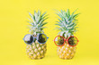 Leinwandbild Motiv Pineapples with red and blue sunglasses on yellow background - Summer background
