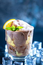 Orange Soda Creamsicle Ice Cream Float In Glass Decorated With Piece Of Orange And Leaves On Mint, Surrounded By Ice Cubes On Stone Table Backdrop