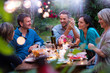 canvas print picture Group of friends gathered around a table in a garden on a summer evening to share a meal and have a good time together