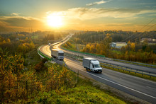 Delivery Van And Truck Driving On The Highway Winding Through Forested Landscape In Autumn Colors At Sunset