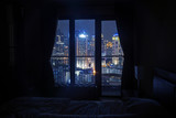 Dark bedroom with light on the skyscrapers