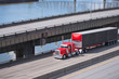 canvas print picture - Classic red big rig semi truck with black semi trailer running on the multilevel overpass road over the river