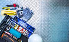 Top View Of Tools Box And Helmet On Checkered Plate Background In Workshop. Service Tools Set. Home Building And Electrical Tools. Plumber Hand Tools. Technician Equipment For Repair Work.