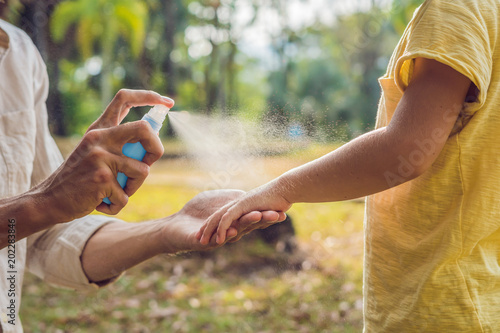 Fototapeta dad and son use mosquito spray.Spraying insect repellent on skin outdoor obraz
